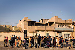 Members of the 1st Infantry, 17th Regiment, stand outside a polling station where they stopped during a patrol of western Mosul, Iraq, Dec. 14, 2005. This is part of an effort to provide security in preparation for Iraq's first post-Saddam parliamentary elections. The western sector is home to Mosul's primarily Sunni population, which has been resistant to the American presence in Iraq.