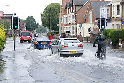 Cars and cyclists drive through flooded street after torrential rain caused flooding in Oxford and the Thames Valley area; July 2007,