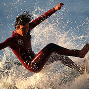 A surfer tries to maintain contact with his board as he crests a wave while surfing near the Huntington Beach Pier on Friday, November 7. Photo by Adam Eberhardt/SSA.