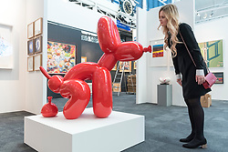 "© Licensed to London News Pictures. 16/01/2018. LONDON, UK. A staff member view ""POPek (red)"" by Sebastian Burdon. Preview day of the 30th anniversary of the London Art Fair.  The fair launches the international art calendar with modern and contemporary art from leading galleries around the world and is taking place at the Business Design Centre, Islington from 17 to 21 January 2018.   Photo credit: Stephen Chung/LNP"