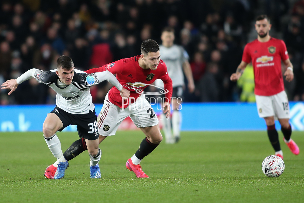 Derby County midfielder Jason Knight  in a tussle for the ball with Manchester United defender Diogo Dalot during the The FA Cup match between Derby County and Manchester United at the Pride Park, Derby, England on 5 March 2020.