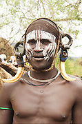 Africa, Ethiopia, Debub Omo Zone, Mursi tribesmen. A nomadic cattle herder ethnic group located in Southern Ethiopia, close to the Sudanese border. A warrior with warthog fangs earring decoration