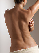Back view of woman caressing her beautiful and graceful nude torso