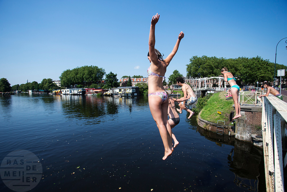 Jongeren springen vanaf de Muntbrug in Utrecht het verkoelende water van het Merwedekanaal in. Op waarschijnlijk de laatste mooie zomerse dag genieten mensen nog volop van de zon.<br />