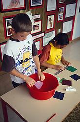 Junior school children investigating how materials shrink during science lesson,