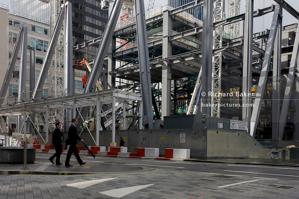 Businessmen and city workers pass beneath a new construction building project in London's financial district, the Square Mile.