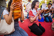 06 JANUARY 2013 - BANGKOK, THAILAND: Women pray at a shrine in Bangkok during a service for a relic of the Buddha's hair. The relic has been on display in Bangkok for about 10 years. There was a ceremony in Sanam Luang in Bangkok Sunday to honor the relic. People prayed for it and received blessings from Buddhist monks and Brahmin priests who presided over the service. The hair is being moved to Ayutthaya, where it will be displayed in a Buddhist temple. The piece of hair has been on loan to Thai Buddhists from a Buddhist temple in Sri Lanka.   PHOTO BY JACK KURTZ