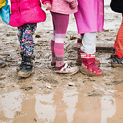 Children queuing in a muddy field for a cup of tea.  Transit camp of Idomeni, Greece. <br /> <br /> Thousands of refugees are stranded in Idomeni unable to cross the border. The facilities are stretched to the limit and the conditions are appalling.