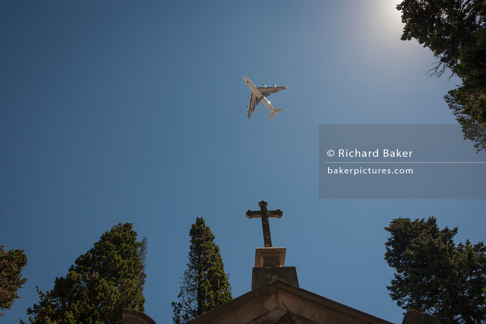 A passing jet airliner flies overhead, above the cross of a family mausoleum, on 14th July 2016, at Prazeres Cemetery, Lisbon, Portugal. Prazeres Cemetery (Cemitério dos Prazeres) is the largest cemetery in Lisbon, Portugal, located in the west part of the city in the former Prazeres parish. It was created in 1833 after the outbreak of a cholera epidemic. Many famous Portuguese citizens are buried here, including artists, authors and government figures, and the cemetery features many large mausoleums built in the 19th century. (Photo by Richard Baker / In Pictures via Getty Images)
