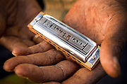 An eldery african-american man shows off his harmonica