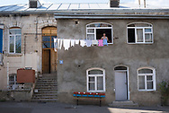 A woman, a little girl beside her, hangs laundry to dry outside their home in Stepanakert, Nagorno-Karabah