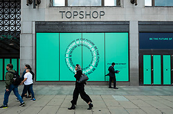 © Licensed to London News Pictures. 30/07/2021. LONDON, UK.  People pass the empty former flagship Topshop store on Oxford Street. According to a report from the British Retail Consortium (BRC) and Local Data Company, one in seven shops across Britain is empty as retailers continue to suffer the effects of the Covid pandemic on footfall and customers move to online shopping.  There is a sharp divide between the south of England, including London, with lower vacancy rates compared to the north of the country.  Photo credit: Stephen Chung/LNP