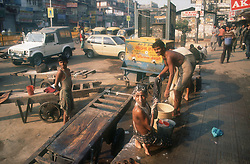 Chandni Chowk; a main shopping street in Delhi; India; with men washing in foreground,
