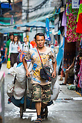 06 JUNE 2013 - BANGKOK, THAILAND:  A porter uses a handtruck to haul clothing in wholesale stalls in Bobae Market in Bangkok. Bobae Market is a 30 year old market famous for fashion wholesale and is now very popular with exporters from around the world. Bobae Tower is next to the market and  advertises itself as having 1,300 stalls under one roof and claims to be the largest garment wholesale center in Thailand.       PHOTO BY JACK KURTZ