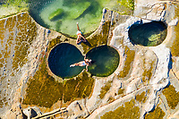 Aerial view of couple floating at figure eight pools at Sydney's Royal National Park, Australia.