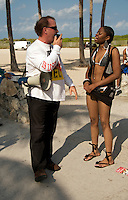 A Pastor preaches on the beach while an observer argues with him during the  2008 Miami Beach Urban Weekend. The Miami Beach Urban weekend in the largest Urban Festival in the World, that caters toward the Hip Hop Generation. Over 300.000 participants make the annual trek to South Beach for 4 days full of fun, food, festivities, entertainment, music, and more.
