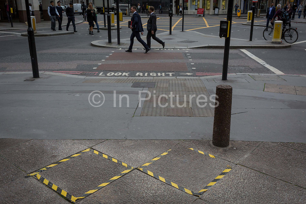 Two businessmen walk past two pavement stones ringed with hazard tape, on 14th September 2017, in the City of London, England.