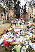 Floral tributes laid around the base of the statue of Nelson Mandela in Parliament Square, London after his death. The statue is a bronze sculpture of former President of South Africa and anti-apartheid activist Nelson Mandela by the artist Ian Walters.