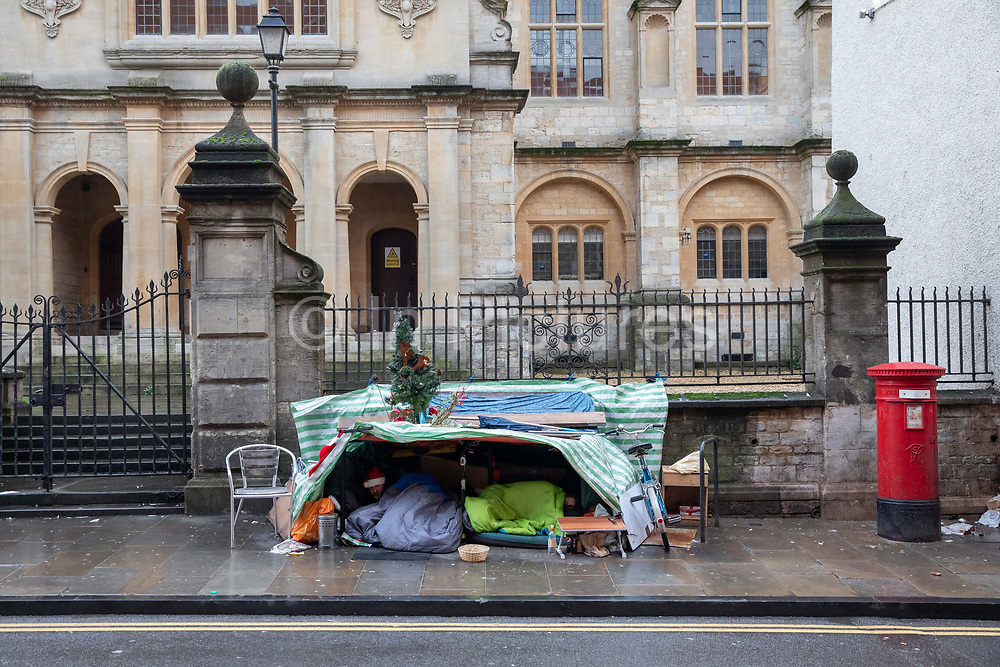 Two homeless men sleeping under a makeshift tent with festive decorations on Christmas Eve on the 24th December 2019 in Oxford in the United Kingdom. Street homelessness has been on the increase in England since 2010.