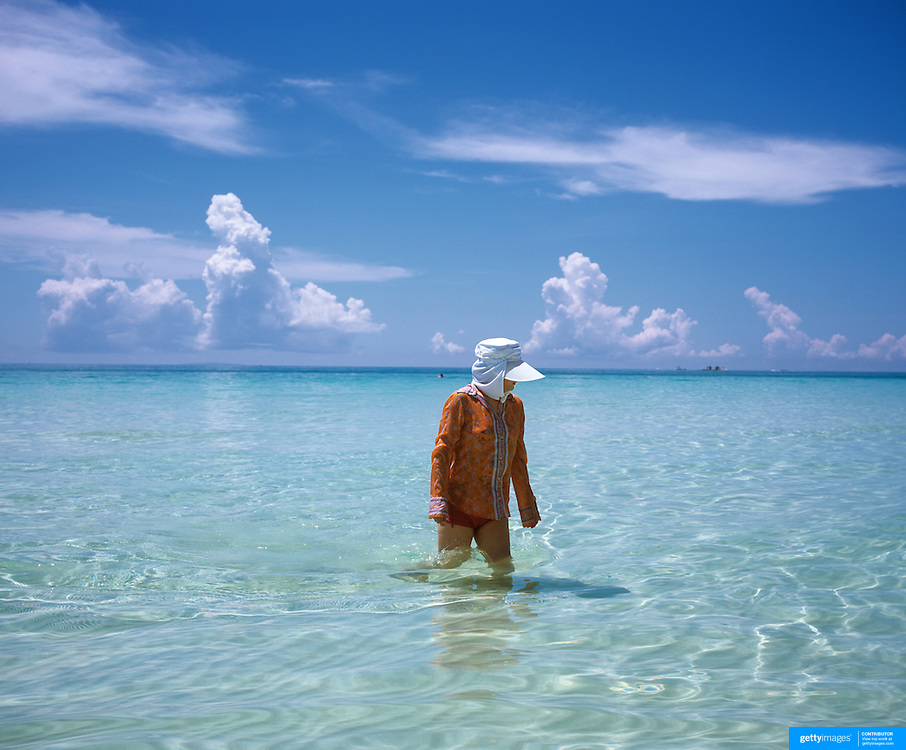 A tourist wears protective clothing to protect herself from the dangers of the sun while in the ocean at White Beach, Boracay Island, The Philippines. 23rd July 2011. Photo Tim Clayton