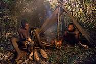Mikea men grating babo roots for their moisture, Madagascar