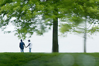 Couple holding hands while walking through waterfront park in the rain, Bellingham Washington