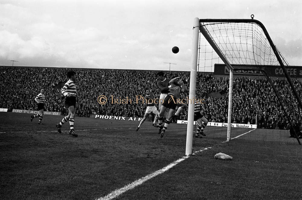 25/04/1965<br /> 04/25/1965<br /> 25 April 1965<br /> F.A.I. Cup Final: Shamrock Rovers v Limerick at Dalymount Park, Dublin. Limerick centre forward Mitchell holds keeper Smyth of Shamrock Rovers as the ball sails over their heads into the net.
