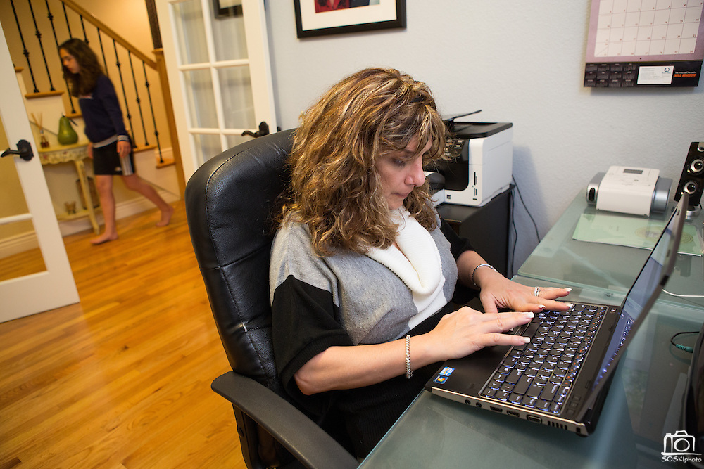 Joy Hahn, Business Development Manager, of Cornerstone Technologies responds to emails before helping her daughter, Jordan, 11, with homework while telecommuting from their home in San Jose, California, on March 25, 2013.  (Stan Olszewski/SOSKIphoto)