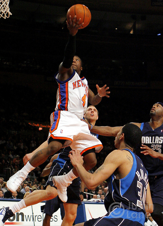 The Knicks' Nate Robinson (L) drives to the basket past the Mavericks' Dirk Nowitzki (2nd from L) Devin Harris (2nd from R) and Eric Dampler (R) during the first half of the game between the Dallas Mavericks and the New York Knicks at Madison Square Garden in New York, New York on Tuesday 20 March 2007.