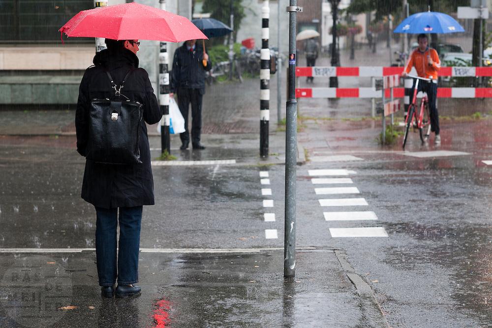 Een vrouw wacht geduldig in de stromende regen voor ze veilig de weg over kan steken.<br /> <br /> A woman is waiting in the rain to cross the street.