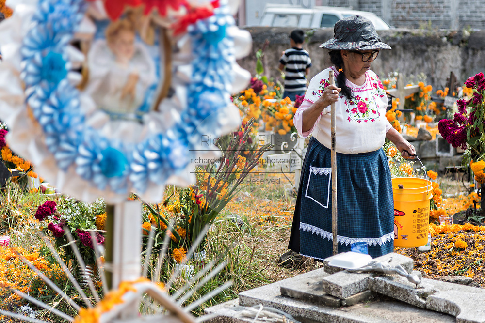 An elderly Purepecha indigenous woman cleans the grave site of a relative during the Day of the Dead festival November 2, 2017 in Ihuatzio, Michoacan, Mexico.  The festival has been celebrated since the Aztec empire celebrates ancestors and deceased loved ones.