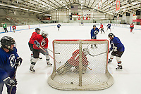 The Blue team slides the puck into the Red teams goal during Lakes Region Woman's Hockey Club at the Laconia Ice Arena Tuesday evening.   (Karen Bobotas/for the Laconia Daily Sun)