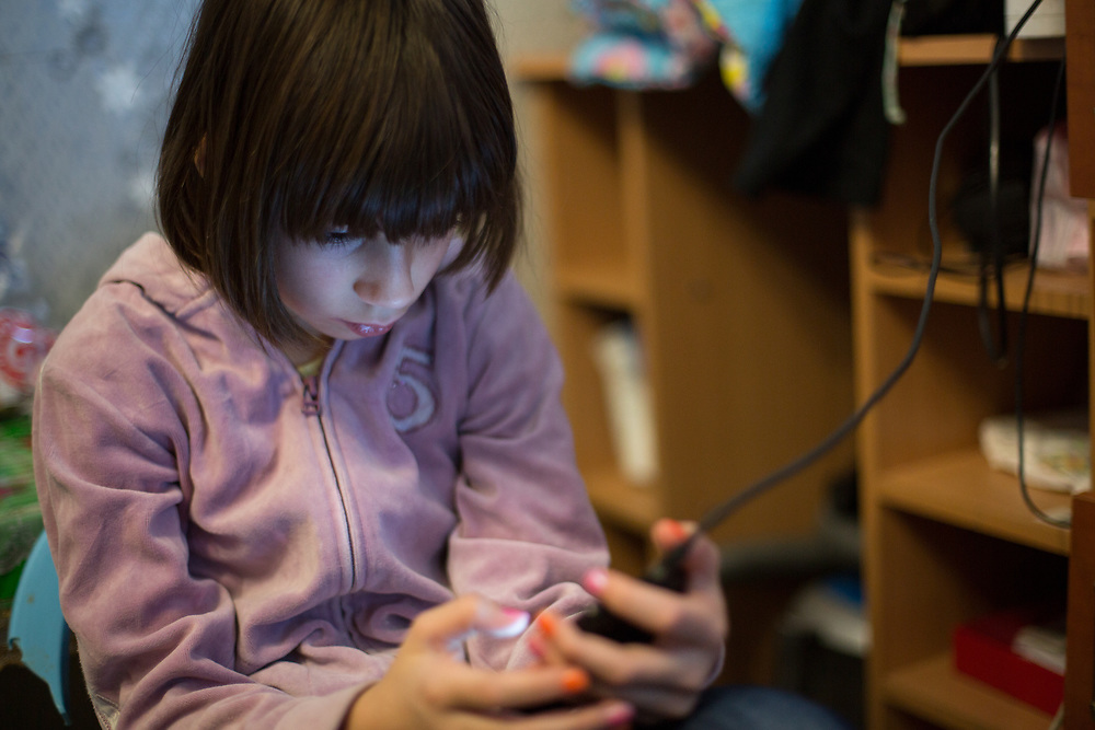 """CAPTION: Masha, engrossed in her mother's phone. During a recent family emergency, Masha stayed with a foster family, arranged by Partnership For Every Child (P4EC). """"It was good there"""", she says. """"Lulya and her daughter were nice. We did drawing and played outside"""". NAMES MUST BE CHANGED. LOCATION: St Petersburg, Russia. INDIVIDUAL(S) PHOTOGRAPHED: Diana Orlova."""