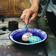 A woman dyeing painted eggs, Hurghis, Bucovina, Romania. In Christian Orthodox countries such as Romania there is a tradition of skilfully painting eggs before Easter. In the villages of Bucovina, the egg painters use a tool called a 'kishitze' a stick with an iron tip, to apply molten wax in the desired pattern to a blown egg. The egg is then dipped in the lightest colour dye to be used. The egg is then heated and the protective wax melts away and a new pattern can be added, then dipped in a different colour and so on.