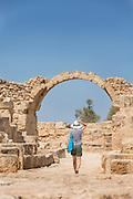 Female tourist walking under arch while exploring ancient ruins, Paphos Archaeological Park, Paphos, Cyprus