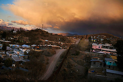 The sun sets on the border fence between Nogales, Arizona at left and Nogales, Mexico at right.  Cities along the US-Mexican border have always existed in their own space, defined more by their position between two countries than their presence in one of them.  With recent increased border security the complexity of these towns is changing. Most immigrants and drug smugglers are looking to the vast desert that straddles Sonora, Mexico and Arizona.  Because this desert is one of the hardest regions to patrol, people looking to cross have been funneled here as security increases in places like Tijuana and Ciudad Juarez.  Nogales, with a population of about 400,000, is the largest city near the desert in Sonora and receives almost all of the deported or repatriated Mexicans who have been caught trying to illegally enter the US.