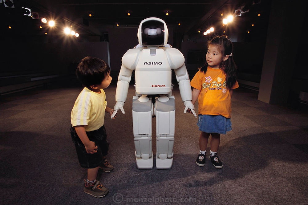Though tentative at first, brother and sister Taichi (3, at left) and Shino (5) warm up to the robot ASIMO (Advanced Step in Innovative Mobility) and agree to stand close enough to get a good look at the small stature robot after a performance at Suzuka City, Japan. Honda's walking robot, called ASIMO, is child-sized and has more maneuverability than it's predecessor, the Honda P3. Pictured here at Suzuka City, Japan, amusement complex..