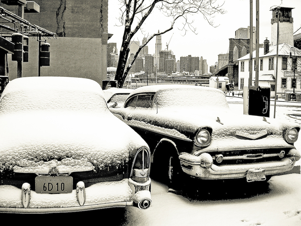 Two old Chevrolet cars covered with snow parked in a garage on Fulton street, Brooklyn, New York, 2008.