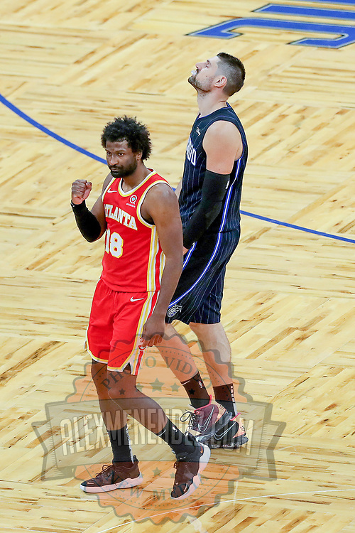 ORLANDO, FL - MARCH 03: Solomon Hill #18 of the Atlanta Hawks celebrates a come from behind victory as Nikola Vucevic #9 of the Orlando Magic scowls during the second half at Amway Center on March 3, 2021 in Orlando, Florida. NOTE TO USER: User expressly acknowledges and agrees that, by downloading and or using this photograph, User is consenting to the terms and conditions of the Getty Images License Agreement. (Photo by Alex Menendez/Getty Images)*** Local Caption *** Solomon Hill; Nikola Vucevic
