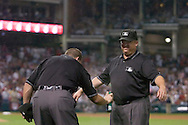 """Major League Baseball umpire Ron Kulpa, left, applies bug spray to umpire Fieldin Culbreth during Game 2 of the 2007 ALDS at Jacobs Field in Cleveland. In what has become known at the """"Bug Game,"""" midges infested the infield during the game but seemed to bother the visiting Yankees more than Cleveland."""