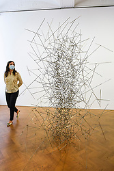 """© Licensed to London News Pictures. 16/06/2020. LONDON, UK. A staff member wearing a facemask views """"Quantum Void V"""", 2009, by Antony Gormley on the opening day of a new exhibition """"Art Basel at Ely House"""" taking place at Galerie Thaddaeus Ropac in Mayfair.  The commercial gallery has implemented social distancing guidelines for visitors for its reopening after coronavirus pandemic lockdown restrictions were relaxed by the UK government.  The exhibition runs 16 June to 31 July 2020.  Photo credit: Stephen Chung/LNP"""