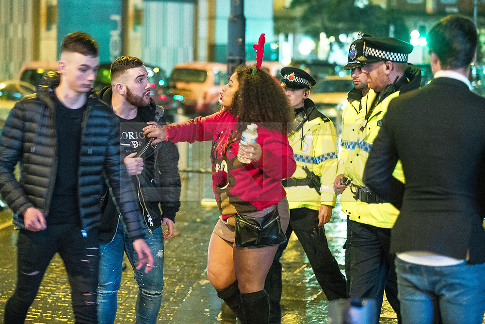 "© Licensed to London News Pictures . 23/12/2017. Manchester, UK. A woman wearing festive red reindeer antlers attempts to encourage a man to leave the area outside the Printworks after police intervene to break up a fight . Revellers out in Manchester City Centre overnight during "" Mad Friday "" , named for being one of the busiest nights of the year for the emergency services in the UK . Photo credit: Joel Goodman/LNP"