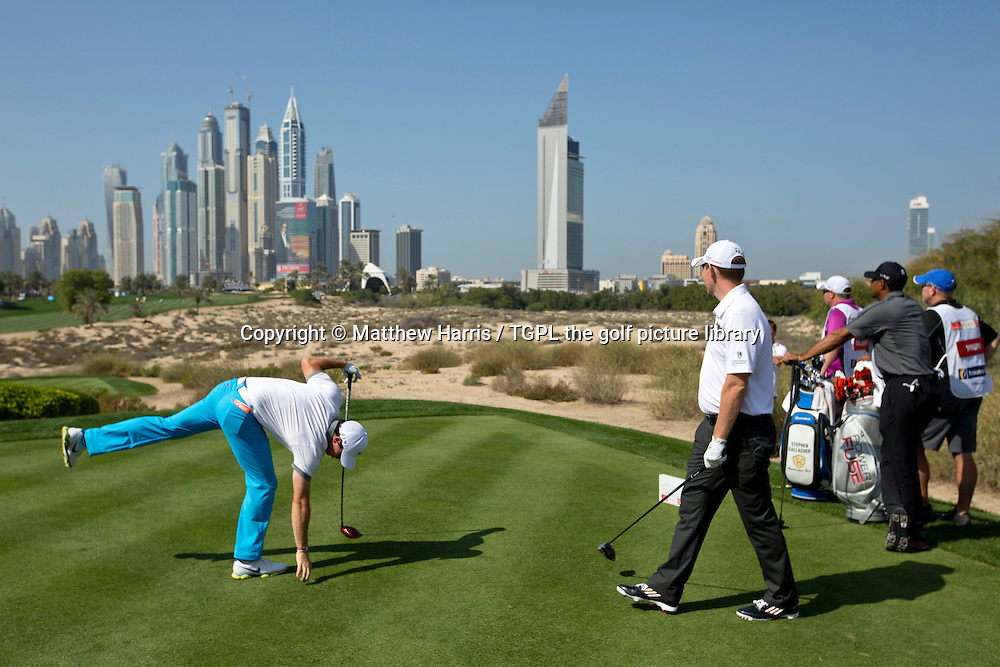 Rory MCILROY (NIR) picks up his tee after driving off the 8th tee as Stephen GALLAGHER (SCO) and Tiger WOODS (USA) look on with the city skyline in the background during first round  Omega Dubai Desert Classic 2014, Emirates Club,Dubai,UAE.