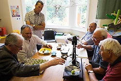 © Licensed to London News Pictures.04/08/15<br /> Egton, UK. <br /> <br /> <br /> Judges sit around a table weighing and classifying the various entries during the annual Egton Gooseberry Show. <br /> There are only two Gooseberry societies left in the country. One in Cheshire and one at Egton in North Yorkshire. The annual show in Egton uses traditional Avoridupois scales to measure the weight of the berries and members of the society are fanatical about trying to grow the best berries each year. <br /> <br /> Photo credit : Ian Forsyth/LNP