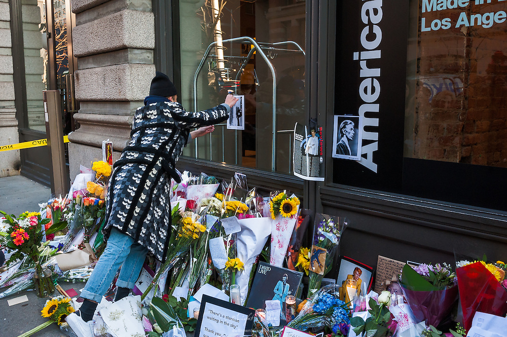 A dedicated fan tapes a photograph of David Bowie to the window of the building that Bowie resided.