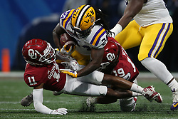 Chris Curry #24 of the LSU Tigers is tackled on a run by Caleb Kelly #19 and Parnell Motley #11 of the Oklahoma Sooners during the first half of the 2019 College Football Playoff Semifinal at the Chick-fil-A Peach Bowl on Saturday, Dec. 28, in Atlanta. (Jason Parkhurst via Abell Images for the Chick-fil-A Peach Bowl)