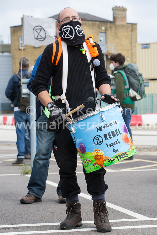 A samba drummer from Extinction Rebellion attends a protest against the expansion of Stansted Airport on 29 August 2020 in Bishop's Stortford, United Kingdom. The activists are calling on Manchester Airports Group to withdraw their appeal, for which planning permission was previously refused by Uttlesford District Council, to be able to expand Stansted Airport from a maximum of 35 million to 43 million passengers a year, as well as calling on the Government to halt all airport expansion in order to maintain its commitments under the Paris Agreement.