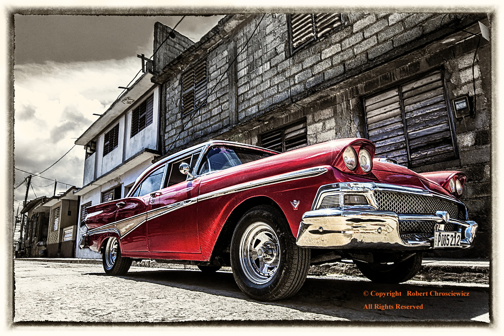 Road Ready Red (B&W&C): A well restored, red, antique automobile stands in stark contrast to the black and white city street in Baracoa Cuba.