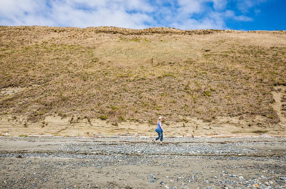 A woman walking on Ebey's Landing BeachTrail below the bluffs, Whidbey Island, Washington, USA.