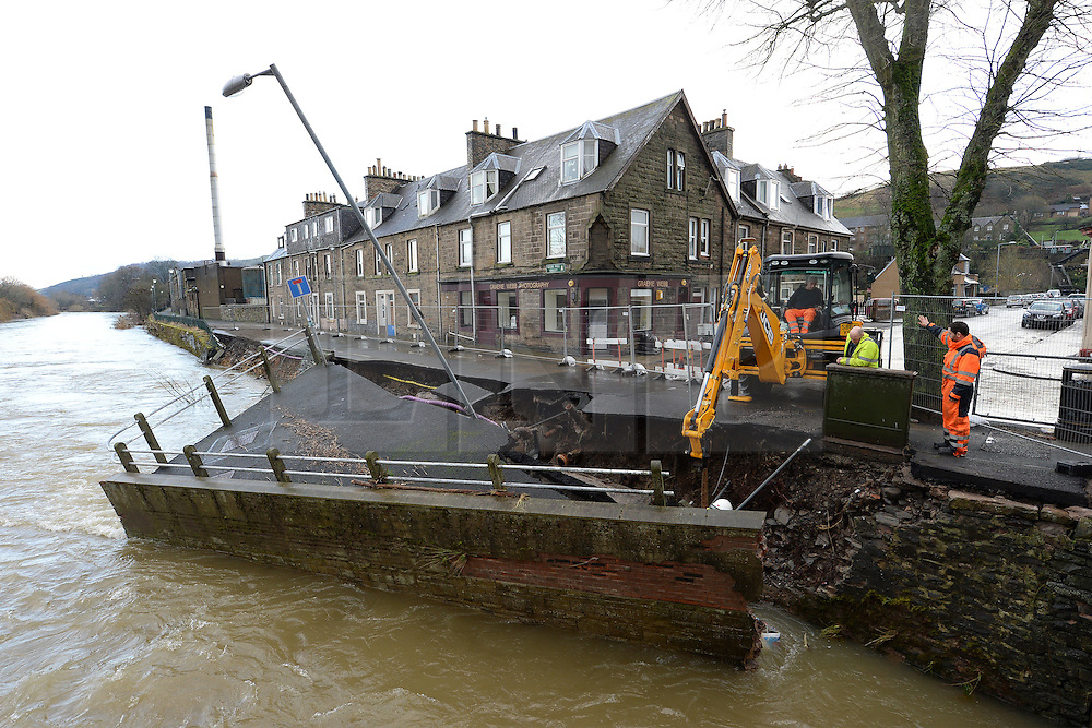 © Licensed to London News Pictures. 07/12/2015. <br /> <br /> Pictured: Workers attempt to repair flood damage to a section of Glebe Mill Street, Hawick, Scottish Borders.<br /> <br /> <br />  Photo credit should read Max Bryan/LNP